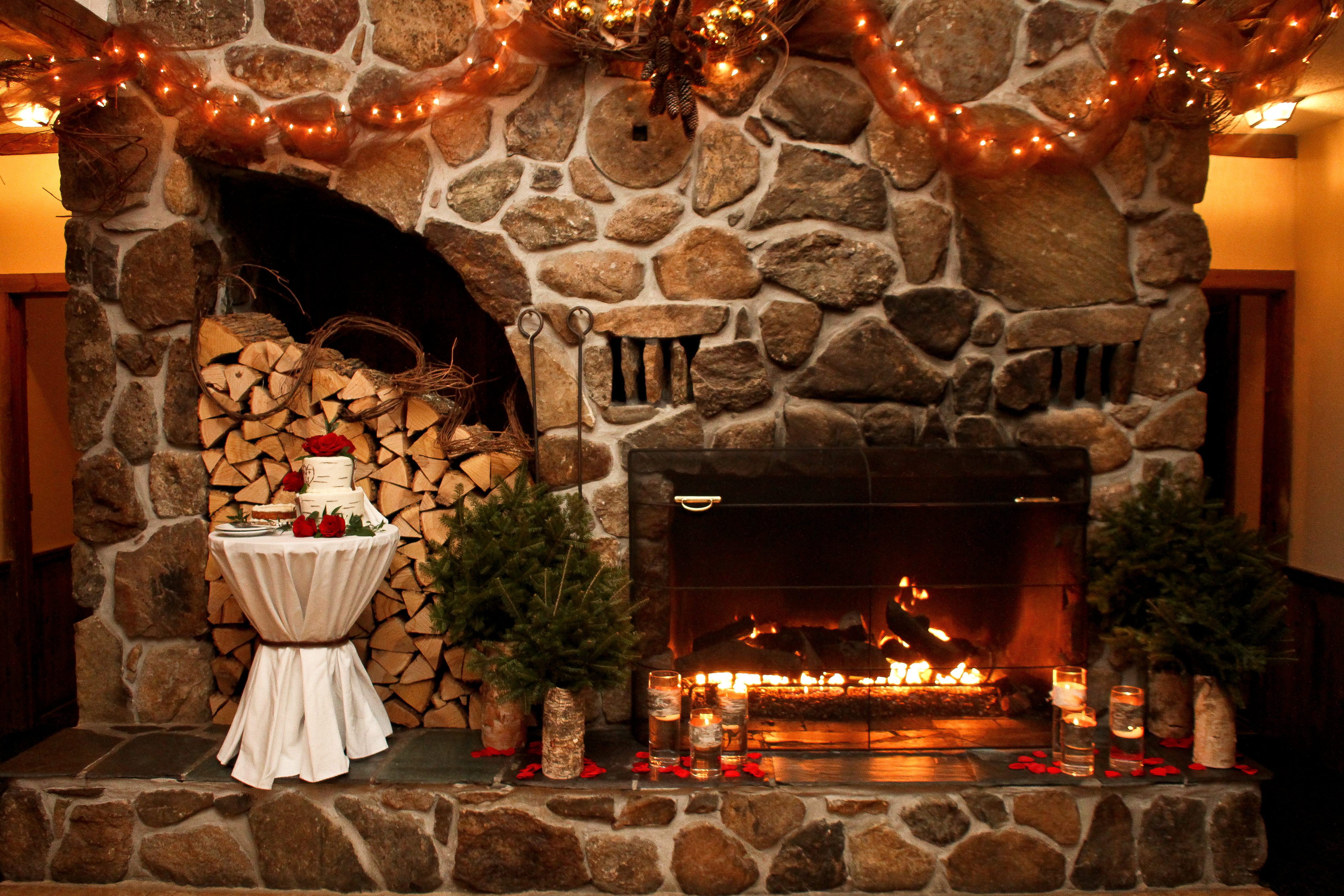 Barn Wedding Venues in NH showcase a stone fireplace and candles